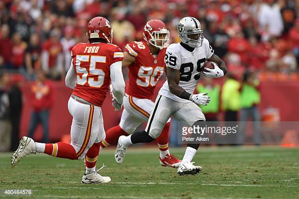 James Jones of the Oakland Raiders runs the ball as Dee Ford and Josh Mauga of the Kansas City Chiefs defend during the first half at Arrowhead...
