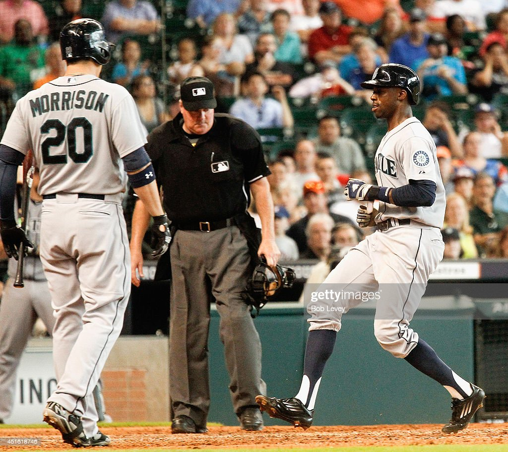 James Jones #99 of the Seattle Mariners scores on a wild pitch in the sixth inning as Logan Morrison #20 and home plate umpire Tim Welke looks on at Minute Maid Park on July 2, 2014 in Houston, Texas.