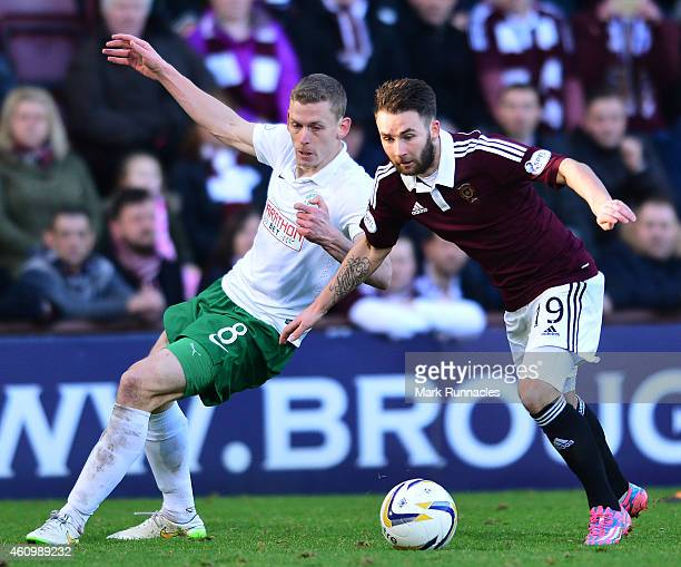 James Keatings of Hearts is tackled by Scott Robertson of Hibernian during the Scottish Championship match between Heart of Midlothian FC and...