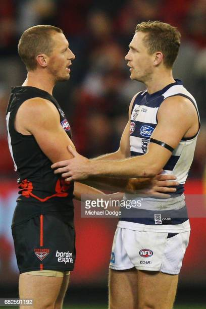 James Kelly of the Bombers celebrates the win on the final siren with former teammate Joel Selwood of the Cats in his 300th match during the round...