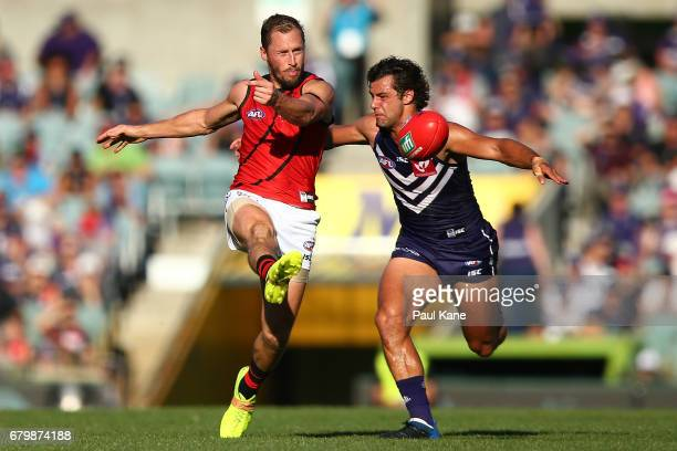 James Kelly of the Bombers gets his kick away before being tackled by Brady Grey of the Dockers during the round seven AFL match between the...