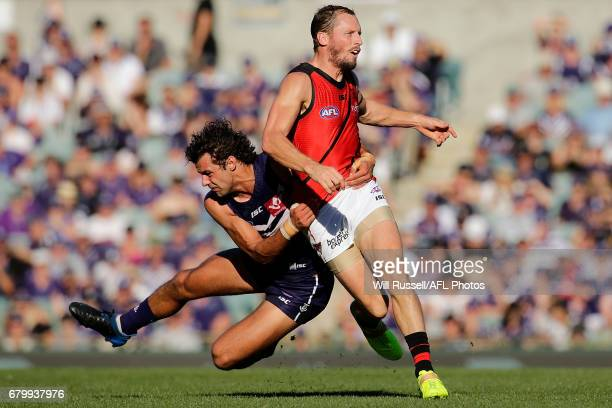 James Kelly of the Bombers is tackled by Brady Grey of the Dockers during the round seven AFL match between the Fremantle Dockers and the Essendon...