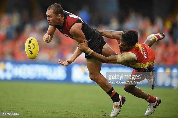 James Kelly of the Bombers is tackled by Jack Martin of the Suns during the round one AFL match between the Gold Coast Suns and the Essendon Bombers...