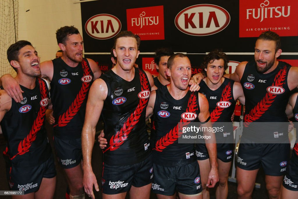 James Kelly of the Bombers (R) sing the club song after winning in his 300th match with James Stewart during the round eight AFL match between the Essendon Bombers and the Geelong Cats at Melbourne Cricket Ground on May 13, 2017 in Melbourne, Australia.