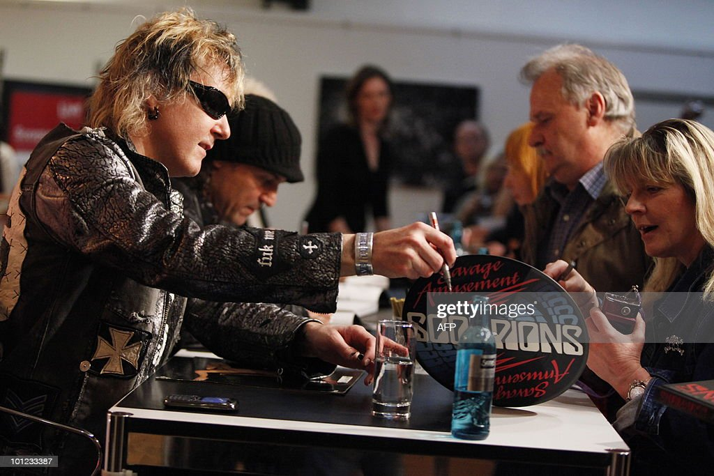 James Kottak (L) of the German rock band Scorpions and other band members sign books for fans after a press conference on May 28, 2010 at the Dussmann bookshop in Berlin during the presentation of a new coffee-table book by photographer Marc Theis. The photographer accompanied the band on their world tour from 2007 to 2009.