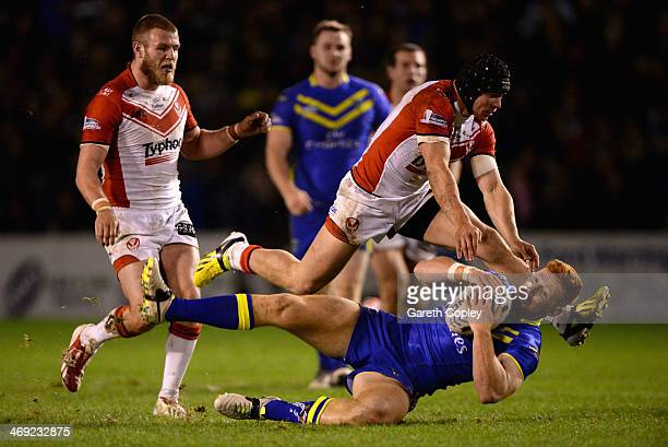 James Laithwaite of Warrington Wolves is tackled by Jonny Lomax of St Helens during the Super League match between Warrington Wolves and St Helens at...