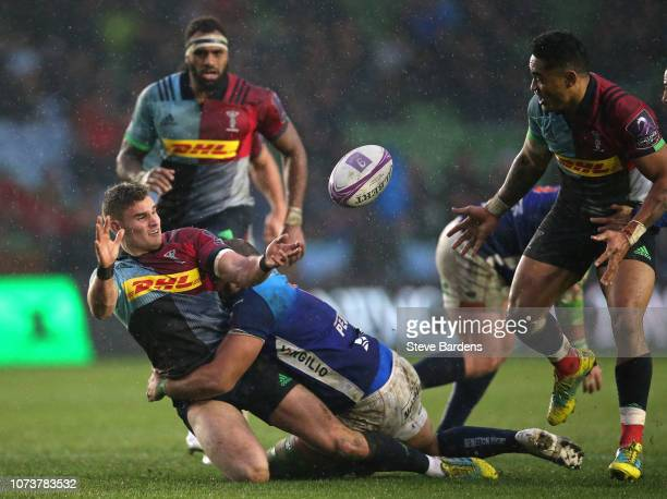 James Lang of Harlequins passes the ball as he is tackled during the European Challenge Cup match between Harlequins and Benetton Rugby at Twickenham...