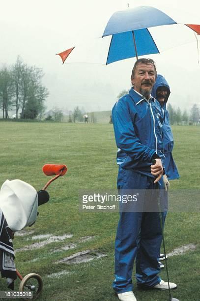 James Last neben den Dreharbeiten zur ARDShow James Last im Allgäu Kempten Golfplatz Sonnenalp RegenSchirm Regenanzug Golfschläger Orchesterchef...