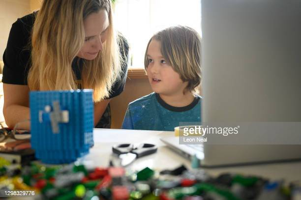 James Laurie, aged 8, is assisted in his online work by his mother Laurette as he continues home schooling, on January 25, 2021 in London, United...