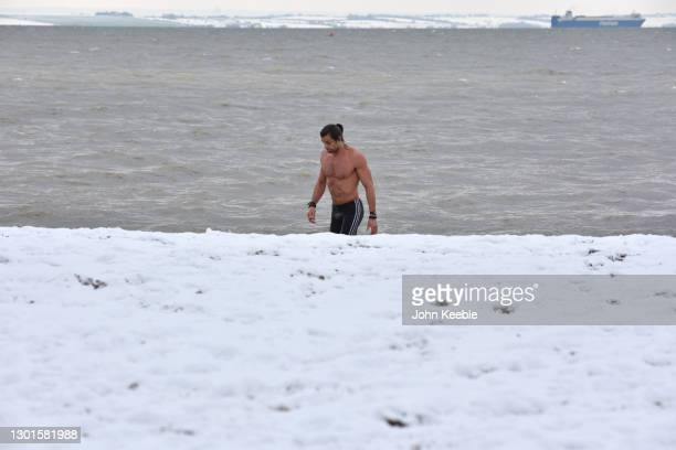 James leaves the water after a cold water swim in the sea at Chalkwell beach after more snow fell overnight on February 11, 2021 in Southend on Sea,...