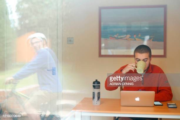 James Lewington drinks a cup of tea while studying his BSc Geography coursework while his father Guy is reflected in the window at their home in...