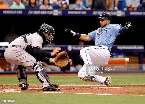 James Loney of the Tampa Bay Rays beats catcher John Ryan Murphy of the New York Yankees to home plate as he scores off of teammate Matt Joyce's...
