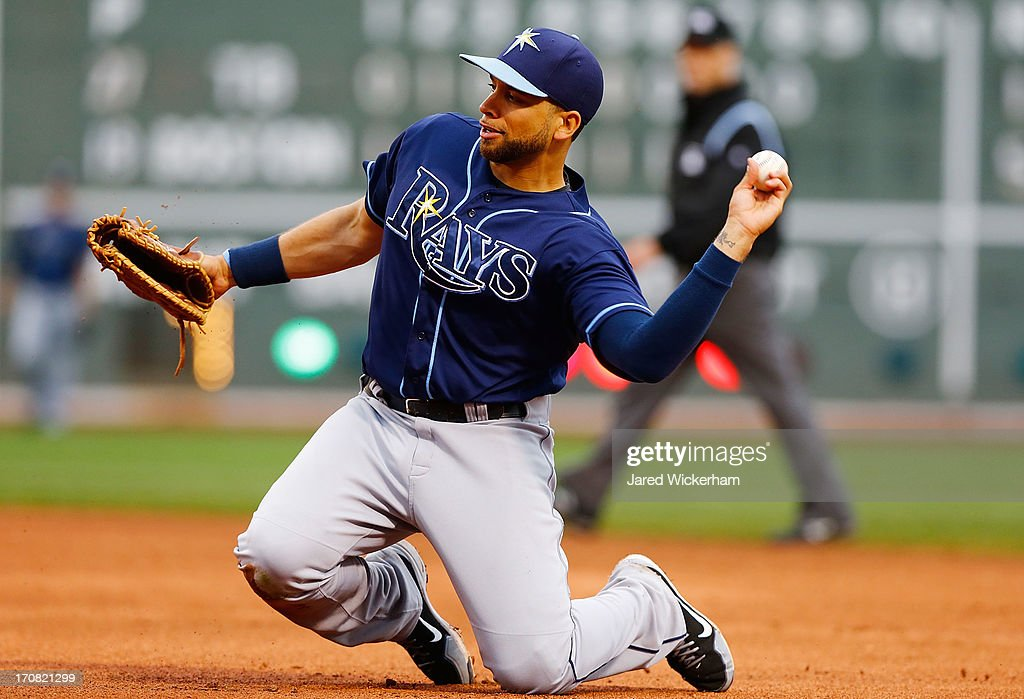 James Loney #21 of the Tampa Bay Rays throws to first base from his knees against the Boston Red Sox during the game on June 18, 2013 at Fenway Park in Boston, Massachusetts.