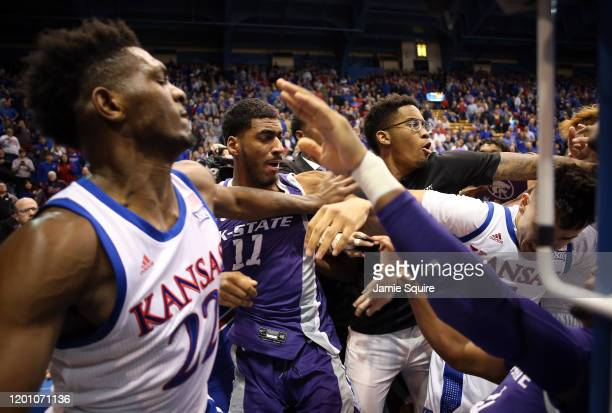 James Love III of the Kansas State Wildcats grabs Elijah Elliott of the Kansas Jayhawks and Silvio De Sousa of the Kansas Jayhawks pushes Antonio...