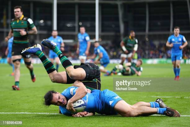 James Lowe of Leinster scores a try despite the challenge from Dan Biggar of Northampton Saints during the Heineken Champions Cup Round 4 match...