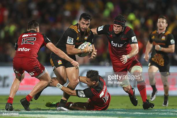 James Lowe of the Chiefs is tackled by Richie Mo'unga of the Crusaders during the round 15 Super Rugby match between the Chiefs and the Crusaders at...