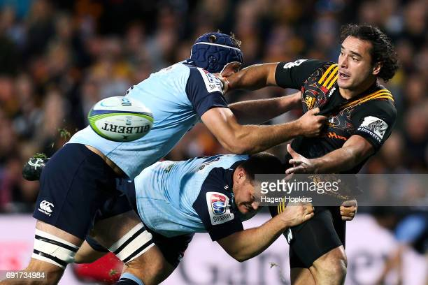 James Lowe of the Chiefs offloads in the tackle of Tom Robertson and Dean Mumm of the Waratahs during the round 15 Super Rugby match between the...