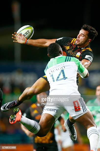 James Lowe of the Chiefs takes the high ball under pressure from Waisake Naholo of the Highlanders during the round 11 Super Rugby match between the...