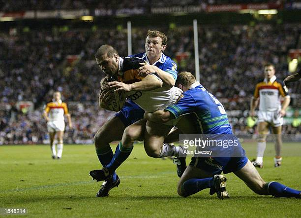 James Lowes of Bradford Bulls is tackled by Mick Higham and Darren Albert of St Helens during the Super League Grand Final held on October 19 2002 at...