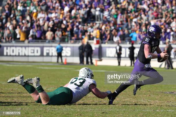 James Lynch of the Baylor Bears trips up Max Duggan of the TCU Horned Frogs on third down in in triple overetime at Amon G Carter Stadium on November...