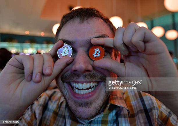 James MacWhyte a member of bitcoin trading club poses with bitcoin medals at the club's meeting in Tokyo on February 27 2014 Bitcoin users in Tokyo...