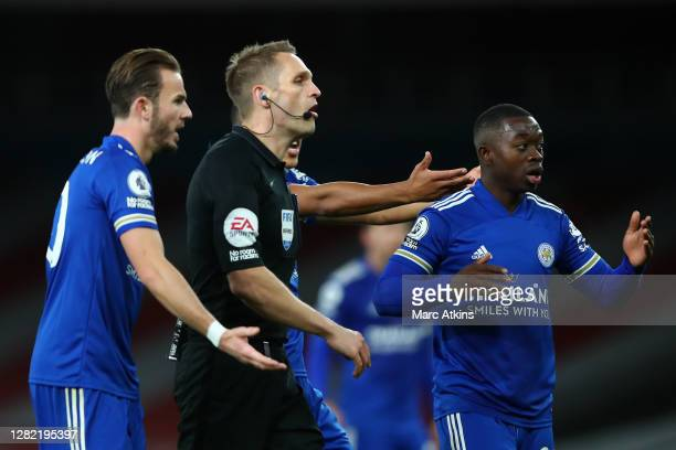 James Maddison and Nampalys Mendy of Leicester City confront referee Craig Pawson after a challenge by Hector Bellerin of Arsenal on James Justin of...