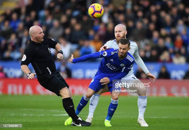 James Maddison of Leicester City challenges for the ball with Aron Gunnarsson of Cardiff City as Match Referee Simon Hooper gets in the way during...