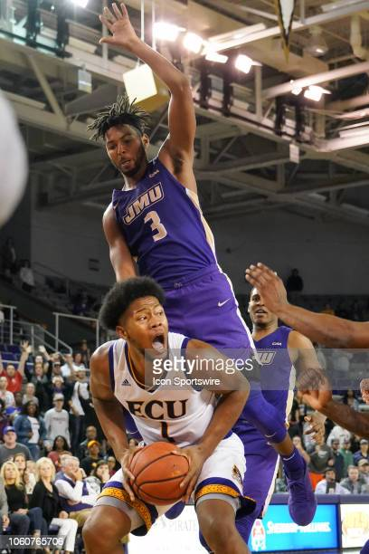 James Madison Dukes guard Stuckey Mosley jumps on the back of East Carolina Pirates forward Jayden Gardner during a game between the East Carolina...