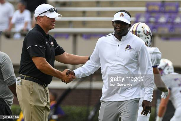 James Madison Dukes head coach Mike Houston and East Carolina Pirates head coach Scottie Montgomery meet before a game between the James Madison...