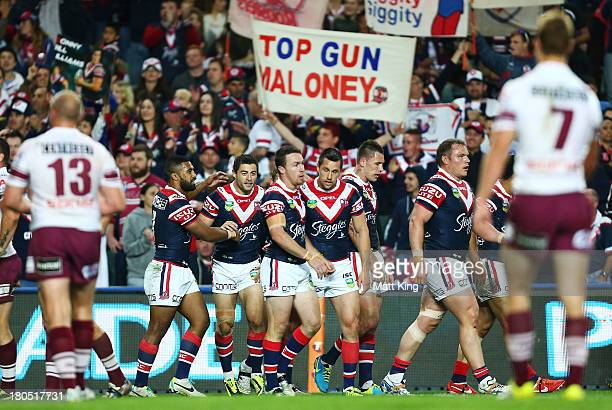 James Maloney and Mitchell Pearce of the Roosters celebrate the try to Roger TuivasaSheck during the NRL Qualifying Final match between the Sydney...