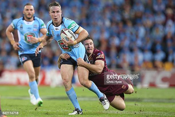 James Maloney of the Blues is tackled by Jacob Lillyman of the Maroons during game two of the State Of Origin series between the Queensland Maroons...