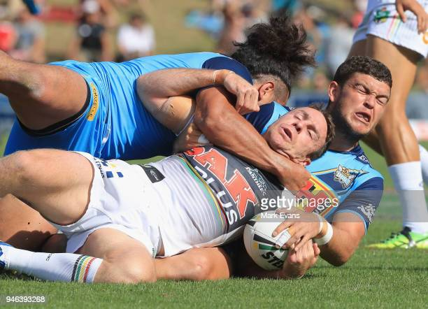 James Maloney of the Panthers is tackled by Ash Taylor and Konrad Hurrell of the Titans during the round six NRL match between the Penrith Panthers...