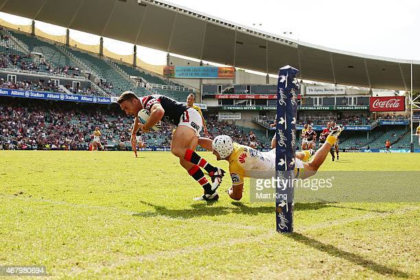 James Maloney of the Roosters beats Jarrod Croker of the Raiders to score a try during the round four NRL match between the Sydney Roosters and the...