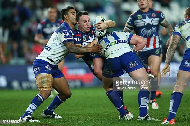 James Maloney of the Roosters is tackled by Bulldog's Joshua Jackson and Michael Lichaa during the round 21 NRL match between the Canterbury Bulldogs...