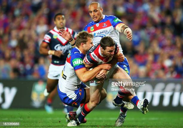 James Maloney of the Roosters is tackled by the Knights defence during the NRL Preliminary Final match between the Sydney Roosters and the Newcastle...