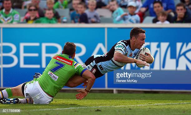 James Maloney of the Sharks scores a try in the tackle of Aidan Sezer during the round seven NRL match between the Canberra Raiders and the Cronulla...