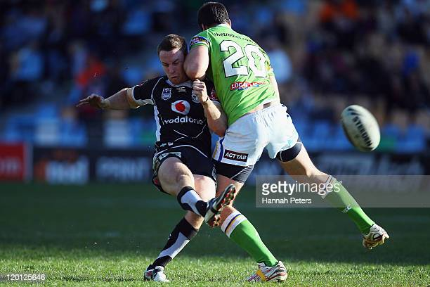 James Maloney of the Warriors is taken out by David Shillington of the Raiders during the round 21 NRL match between the New Zealand Warriors and the...
