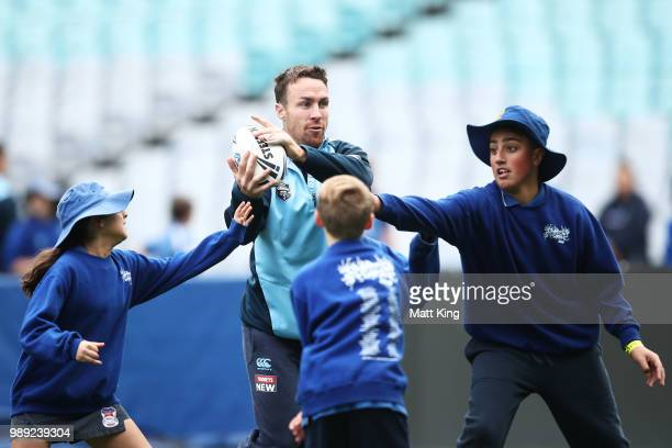 James Maloney takes part in a juniors coaching clinic during the New South Wales Blues State of Origin Team Announcement at ANZ Stadium on July 2...