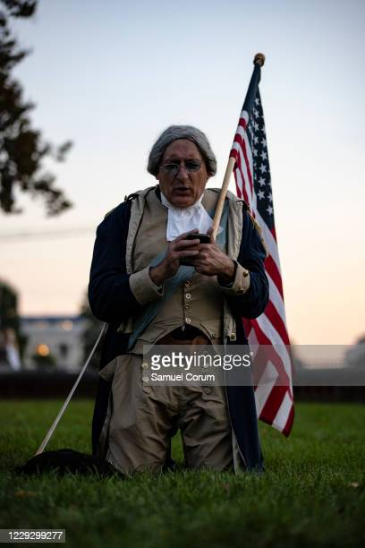 James Manship, dressed as George Washington, recites Washingtons final prayer off of his cell phone while kneeling on the lawn of the US Capitol with...