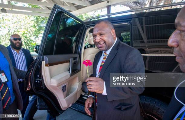 James Marape holds a flower from a well wisher as he leaves the house of Governor General Bob Dadae after being sworn in as the new Prime Minister of...