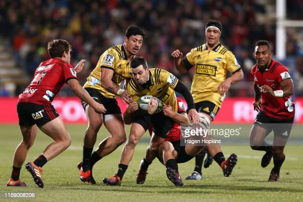James Marshall of the Hurricanes is tackled by Braydon Ennor of the Crusaders during the Super Rugby Semi Final between the Crusaders and the...