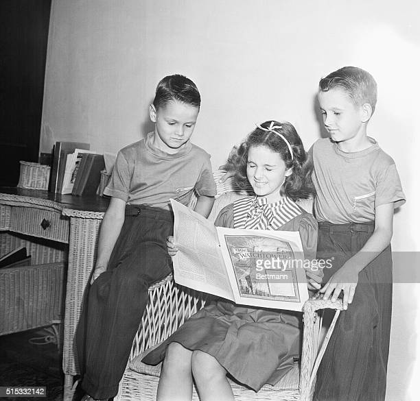 James Mary and Max Morris children of Mr and Mrs Max Morris of Miami are shown at their home reading a publication of the religious sect known...