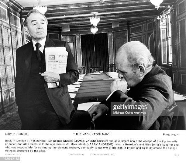 James Mason shows a newspaper to Harry Andrews in a scene from the film 'The MacKintosh Man', 1973.