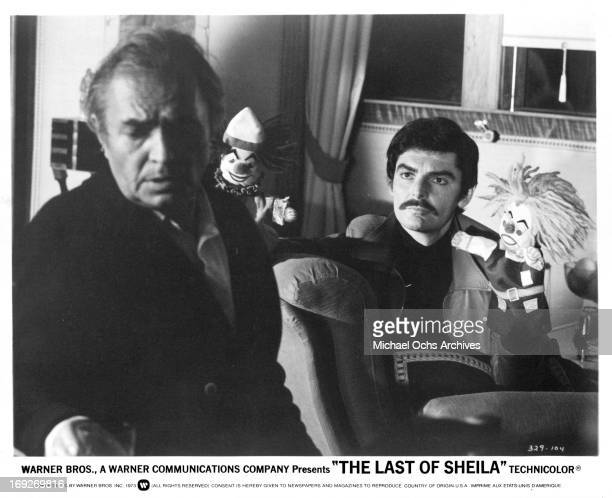 James Mason with his back to puppet holding Richard Benjamin in a scene from the film 'The Last Of Sheila', 1973.