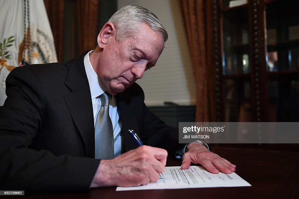 James Mattis signs his confirmation letter to be named US Secretary of Defense in Vice President Mike Pence's Ceremonial Office in the Old Executive Office Building in Washington, DC, January 20, 2017. / AFP / JIM