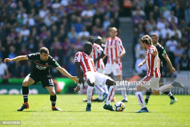 James McArthur of Crystal Palace and Joe Allen of Stoke City look on as Badou Ndiaye of Stoke City controls the ball during the Premier League match...