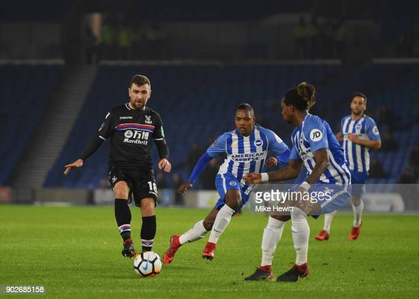 James McArthur of Crystal Palace is faced by Gaetan Bong and Jose Izquierdo of Brighton and Hove Albion with empty seats as a backdrop during The...