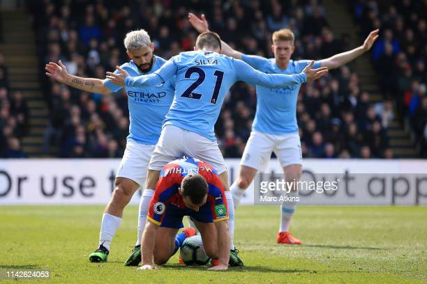 James McArthur of Crystal Palace shields the ball as David Silva Sergio Aguero and Kevin De Bruyne of Manchester City appeal during the Premier...