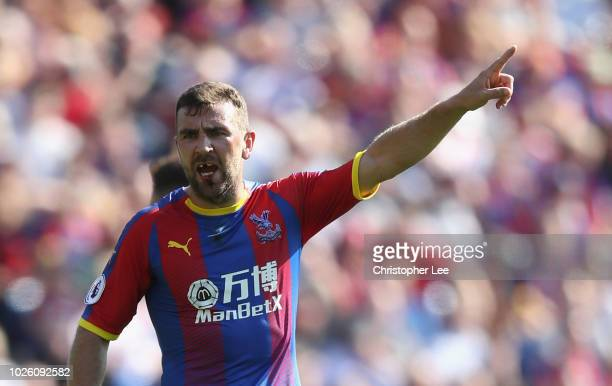 James McArthur of Crystal Palace shouts orders to his team mates as it looks like he is missing his front teeth after a previous challenge during the...