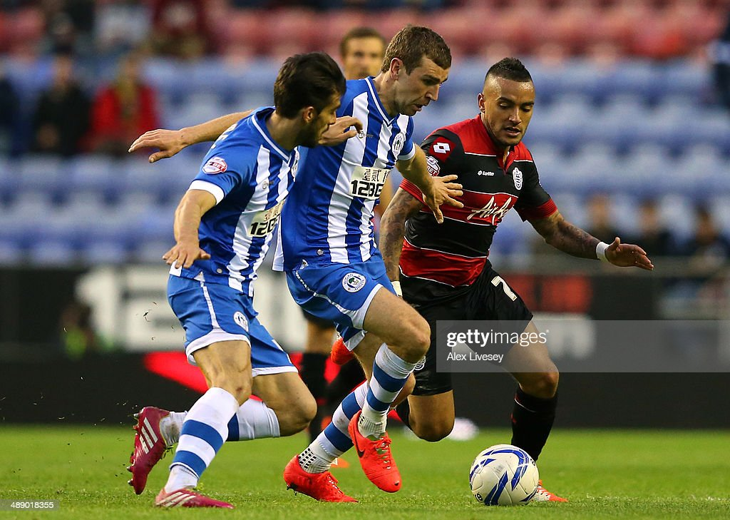 James McArthur of Wigan Athletic holds off a challenge from Danny Simpson of Queens Park Rangers during the Sky Bet Championship Play Off Semi Final first leg match between Wigan Athletic and Queens Park Rangers at DW Stadium on May 9, 2014 in Wigan, England.
